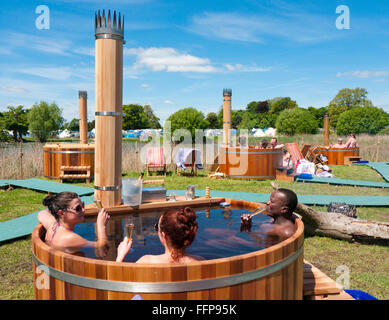 People drinking champagne in a hot tub powered by a built in wood burner at a festival in Britain - Stock Image