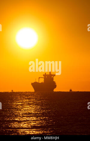 An offshore freighter greets the sunrise near Fort Lauderdale Beach in South Florida. - Stock Image