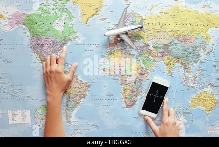 Top view of young tourist woman pointing her next travel destination using world map and mobile phone compass app - Stock Image
