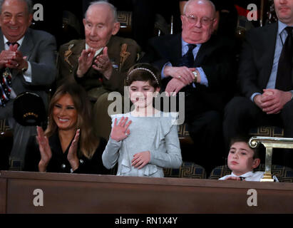 February 5, 2019 - Washington, District of Columbia, U.S. - Grace Eline, who was diagnosed with Germinoma, a germ-cell brain tumor, waves to the audience after being introduced by United States President Donald J. Trump during his second annual State of the Union Address to a joint session of the US Congress in the US Capitol in Washington, DC on Tuesday, February 5, 2019. Grace recently finished chemotherapy and currently shows no evidence of the disease. First lady Melania Trump applauds at left. Joshua Trump, a sixth grader who was bullied at school because of his last name is pictured a - Stock Image