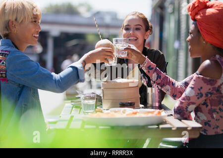 Young women friends toasting water glasses at dim sum lunch at sunny sidewalk cafe - Stock Image