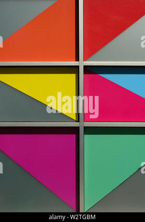 Bright colorful angled shapes in windows on the side of a building - Stock Image