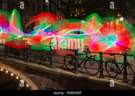 Light painting in Amsterdam, Netherlands, canal Reguliersgracht on a bridge with bicycles. Colourful light. - Stock Image