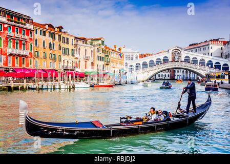Venice, Italy - February 2018: Gondola on the Grand Canal, Ponte Rialto waterfront, landmark of Venice. - Stock Image