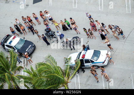 Miami Beach Florida North Beach Ocean Terrace male strip club movie shoot dancers actors extras woman women police car scene - Stock Image