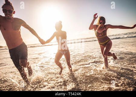 Friends caucasian group of people man and two women enjoy and have fun together in friendship during summer vacation running out of the water - sunset - Stock Image