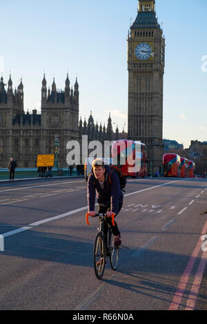 Cyclict and red London buses with Big Ben in the background, London, UK. - Stock Image