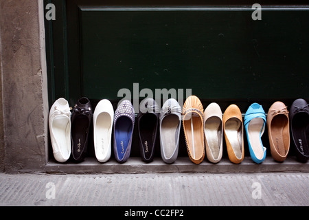Line of flat shoes or 'pumps' propped up against a shop door - Stock Image