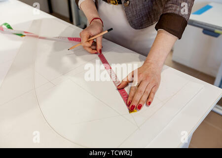 Female hands marking out a pattern on a white table - Stock Image