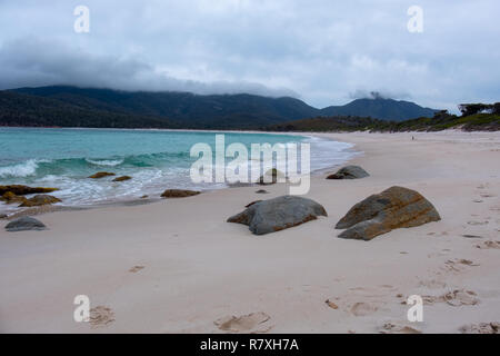 Beach at Wineglass Bay, Freycinet National Park, Tasmania with rocks in the foreground and blue sea on a cloudy day - Stock Image
