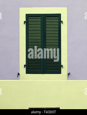 Details of old medieval style building. The building has grey concrete walls and the window frames yellow and green and made of wood. - Stock Image