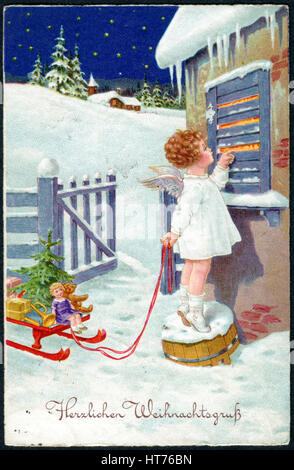 A Christamas postcard printed in Germany, shows a little girl in the image of an angel with gifts. The inscription - Stock Image