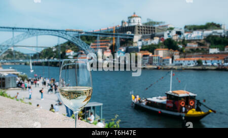 Selective focus of white wine glass overlooking Cais da Ribeira and Ponte de Dom Luis I on the River Douro in Porto, Portugal - reflection of bridge o - Stock Image