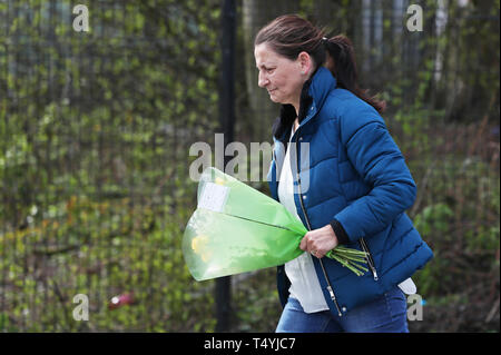 A woman carries flowers to the scene in Londonderry, Northern Ireland, where 29-year-old journalist Lyra McKee was shot and killed when guns were fired and petrol bombs were thrown in what police are treating as a 'terrorist incident'. - Stock Image