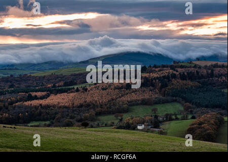 A temperature inversion causes clouds to roll dramatically down towards a lonely farmhouse on the Welsh borders (Stonewall Hill, Knighton, Powys, UK) - Stock Image
