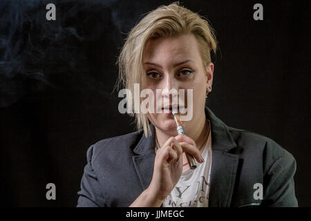 Confused and surprised woman holding electronic cigarette between her teeth - Stock Image