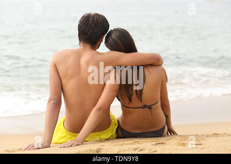 Back view portrait of a couple hugging falling in love looking at ocean sitting on the sand on the beach - Stock Image