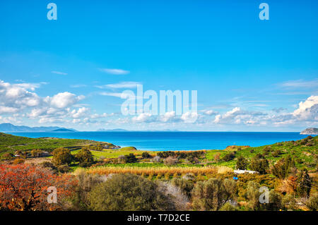 Wide angle meadow field landscape with spring color trees and bushes, blue sea, sky and clouds in Gumusluk, Bodrum Mugla Turkey - Stock Image