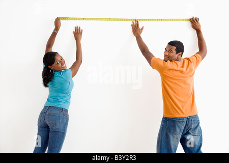 African American male and female measuring wall and looking at viewer - Stock Image