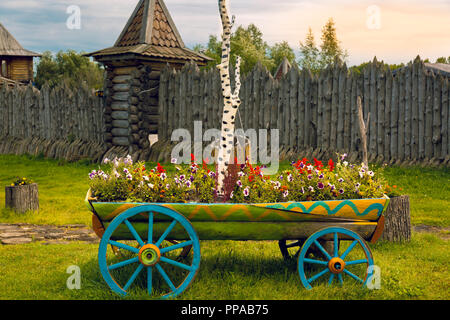A cart full of flowers close-up on a green lawn - Stock Image