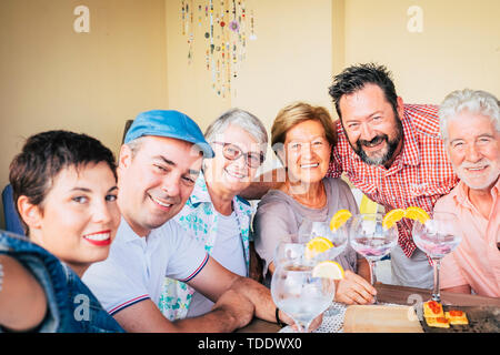Cheerful group of mixed ages friend portrait - young adult and senior caucasian people smile at the camera and hug eachother having fun together - foc - Stock Image