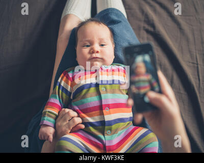 A mother is using her smartphone to take a photo of her baby - Stock Image