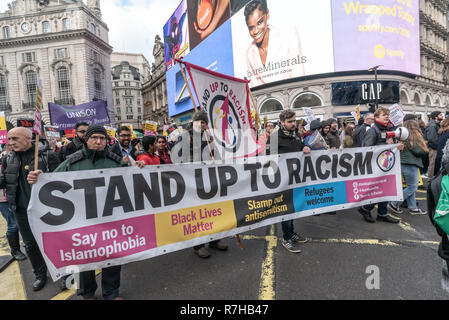 London, UK. 9th Dec, 2018. People carry a Stand Up to Racism banner on the united counter demonstration by anti-fascists in opposition to Tommy Robinson's fascist pro-Brexit march. The march which included both remain and leave supporting anti-fascists gathered at the BBC to to to a rally at Downing St. Police had issued conditions on both events designed to keep the two groups well apart. Credit: Peter Marshall/Alamy Live News - Stock Image
