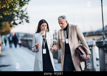 Mature man and young woman business partners walking by a river in city of Prague, talking. - Stock Image