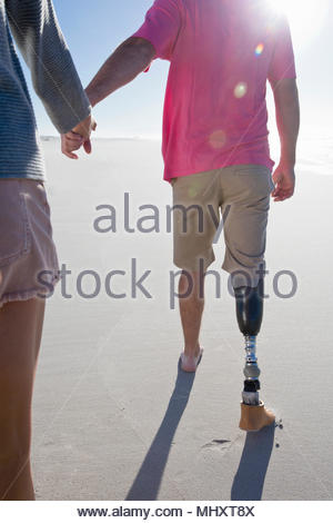 Close Up Shot Of Man With Artificial Leg Walking Along Beach Holding Hands With Female Partner On Summer Vacation - Stock Image