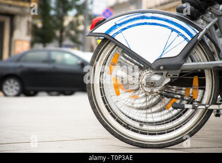 Healthy, ecological transport concept. Rental bikes parking lot. Row bicycle wheels in the city sidewalk - Stock Image