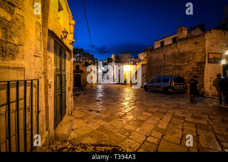 A dog stands under a street light in the distance late night in the old town area of Matera, Italy - Stock Image