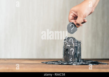 Hand holding a black paper cut with question mark putting or collecting it from a jar. concept of FAQ, questions, mystery and choices - Stock Image
