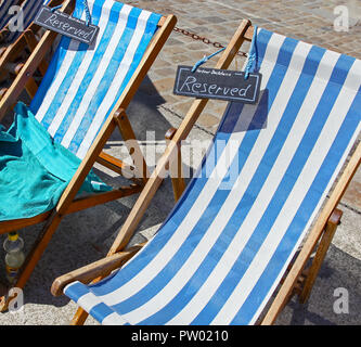 Two deckchairs which have been reserved on St. Ives Harbour, St. Ives, Cornwall, England, UK - Stock Image