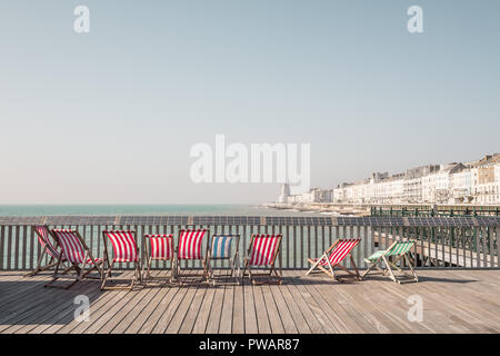 Deckchairs on the Pier at Hastings, East Sussex, UK - Stock Image