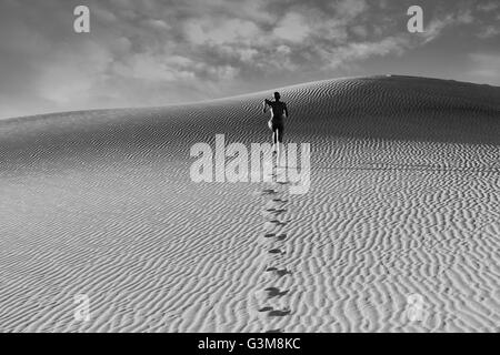 Nude woman running in dessert leaving footprints - Stock Image