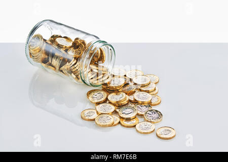 £1 Coins Falling from a Glass Saving Jar - Stock Image