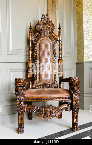 An old, intricately carved oak wood chair with leather upholstering in a stately home. - Stock Image