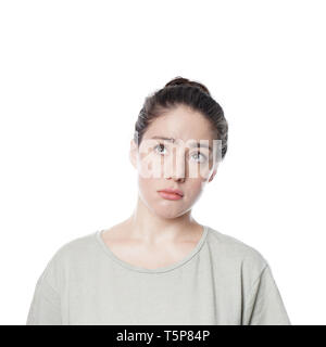worried thoughtful young woman with concerned look on her face looking up contemplating idea or problem - isolated on white background - Stock Image
