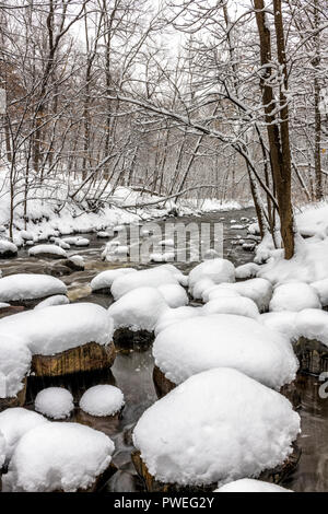 A spring snow storm covers rocks along Nine Mile Creek. - Stock Image