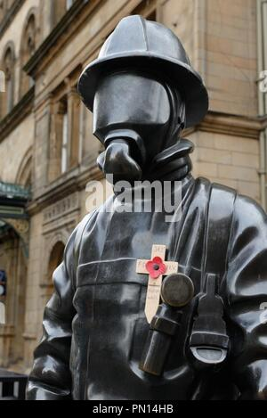 The Citizen Firefighter bronze tribute statue adorned with a wooden cross and poppy dedication to the 911 fatalities Glasgow, Scotland, UK. - Stock Image
