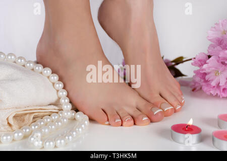 Girl bare feet with french pedicure on white towel and decoration candle, pearls and pink flower in beauty studio isolated on white background - Stock Image