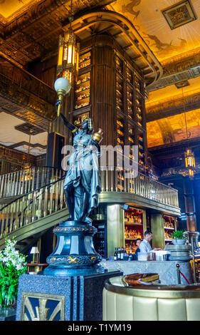 Bronze sculpture by tall cabinet or gin tower the centerpiece of the Atlas bar in the lobby of Parkview Square Singapore. - Stock Image