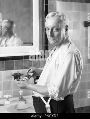 1920s SENIOR MAN STANDING IN SHIRT SLEEVES AT BATHROOM  SINK LOOKING AT CAMERA SQUEEZING GROOMING PRODUCT FROM TUBE INTO HAND   - b10305 HAR001 HARS EXPRESSIONS MIDDLE-AGED B&W MIDDLE-AGED MAN EYE CONTACT GROOMING BEFORE STARING OLDSTERS OLDSTER STRENGTH CHOICE KNOWLEDGE PRIDE AT IN INTO ELDERS SHIRT SLEEVES CONNECTION STARE STYLISH GRAY HAIR INTENSE PENETRATING SQUEEZING BLACK AND WHITE CAUCASIAN ETHNICITY HAR001 NEUTRAL OLD FASHIONED QUIZZICAL - Stock Image