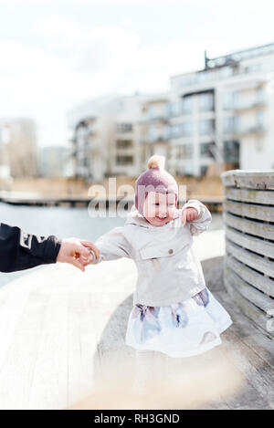 Smiling girl holding parents hand - Stock Image