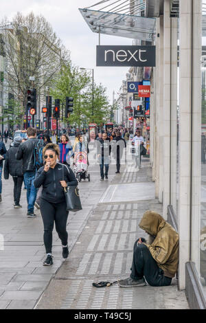 People passing a man begging on Oxford Street in London's West End. - Stock Image