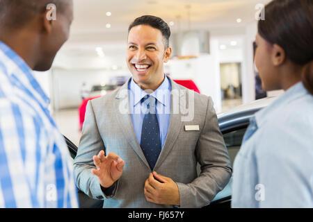 handsome vehicle dealer talking to customers in showroom - Stock Image
