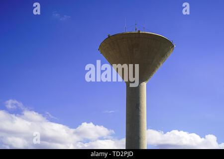 Concrete water tower on blue sky background - Stock Image