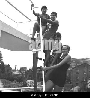 1967, girl swimmers standing on a slide at outdoor lido, England, UK. - Stock Image