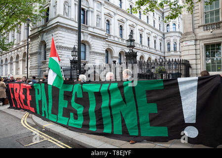 London, UK. May 11th 2019. National Demonstration for Palestine. Thousands of activists marched from Portland Place to Whitehall. Organised by the Palestine Solidarity Campaign, Stop the War Coalition, Palestinian Forum in Britain, Friends of Al- Aqsa & Muslim Association of Britain. Pictured, protesters outside Downing Street with banner stating Stop Arming Israel. Credit: Stephen Bell/Alamy Stock Photo - Stock Image