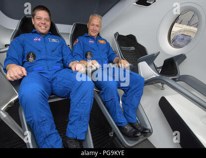 NASA astronauts Bob Behnken, left, and Doug Hurley, assigned to fly on the first test flight of SpaceX's Crew Dragon, pose inside a mockup of the spacecraft at NASA's Johnson Space Center in Houston, Texas on Aug. 2, 2018 ahead of the agency's announcement of their commercial crew assignment Aug. 3.  Nine U.S. astronauts were selected for commercial crew flight assignments on the first test flights and operational missions for Boeing's CST-100 Starliner and SpaceX's Crew Dragon. - Stock Image